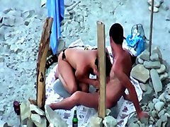 raven haired chick was caught sucking her man at the beach on spy cam